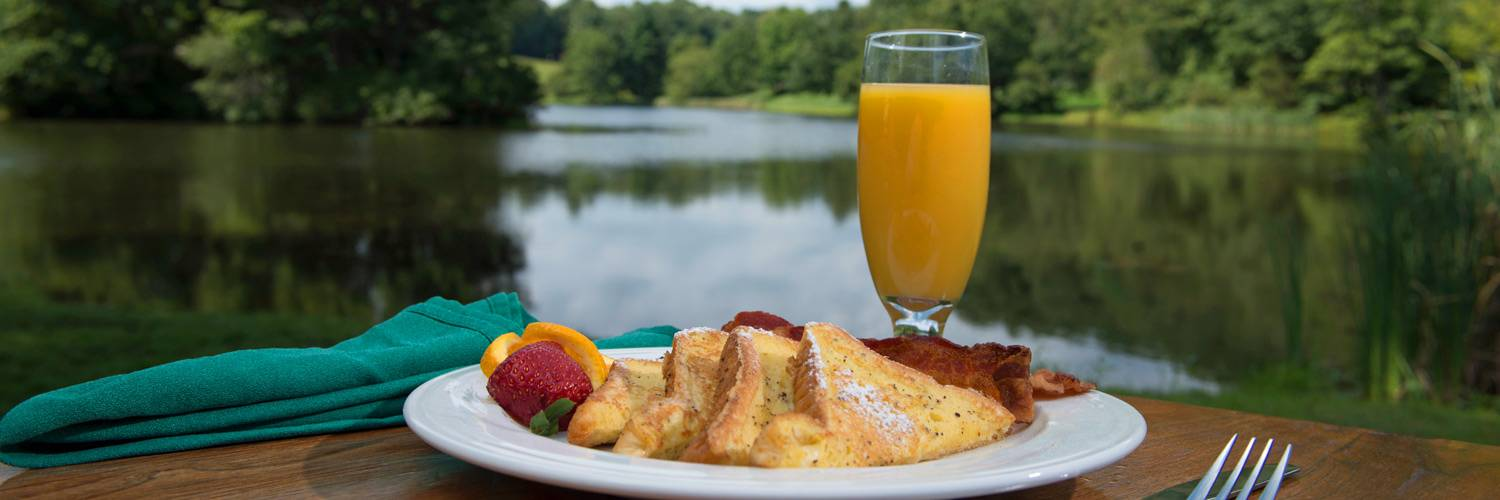 A breakfast plate with French Toast, Bacon, and Orange Juice at Peaks of Otter Lodge