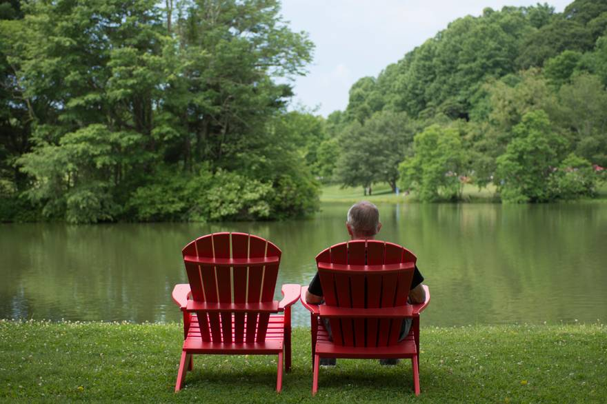 Man in Adirondack Chair Beside Abbott Lake at Peaks of Otter Lodge
